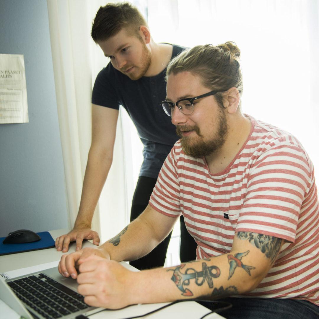 Mies työskentelee kannettavalla tietokoneella, vieressään toinen mies katsomassa työn kulkua.