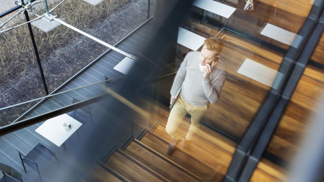 Kännykkään puhuva mies kävelee portaita ylös.