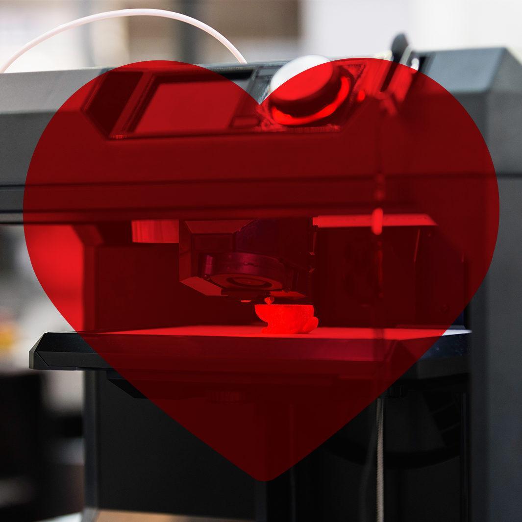 3d-tulostin ja kuvan päällä punainen sydän.