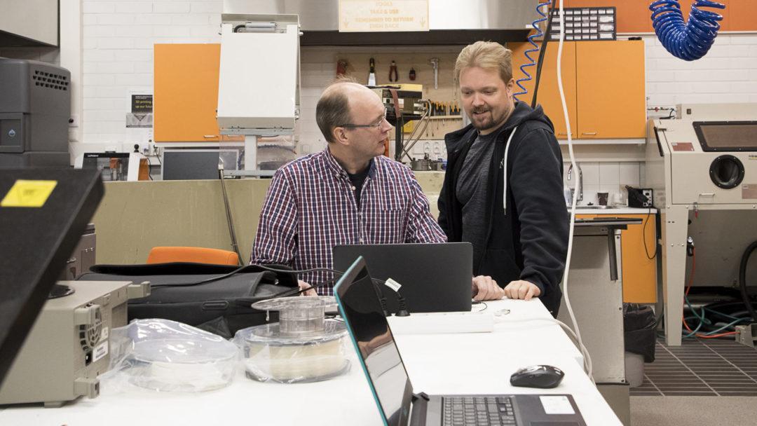 FabLab. Kaksi miestä kannettavan tietokoneen ääressä. Taustalla huoneessa erilaisia työkoneita.