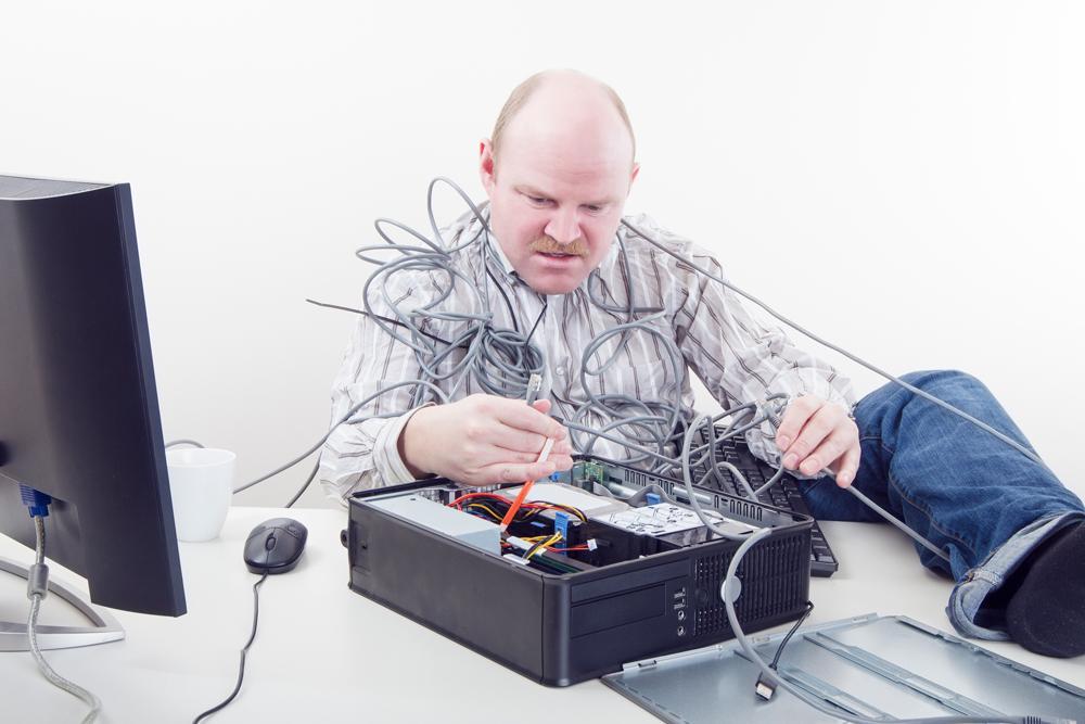 Mies yrittää korjata tietokonetta.